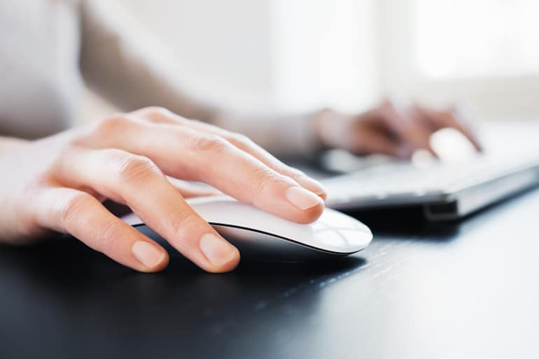 Woman clicking wireless mouse; digital wellness concept