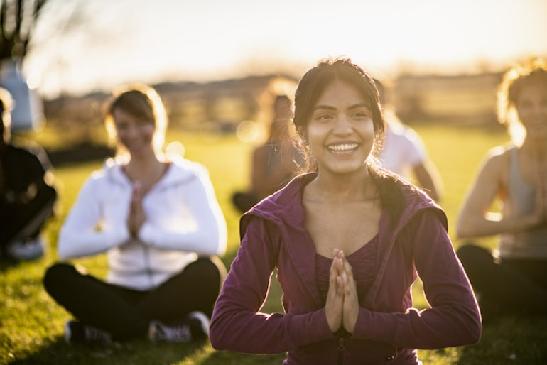 Group of people meditating in park, with girl smiling from the brain benefits of meditation