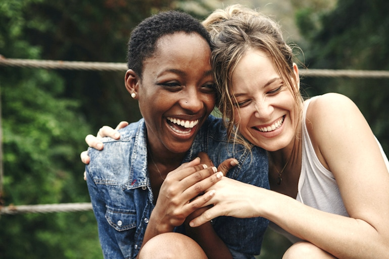Two girl friends laughing, illustrating that psychological benefits of minimalism are happiness and less loneliness
