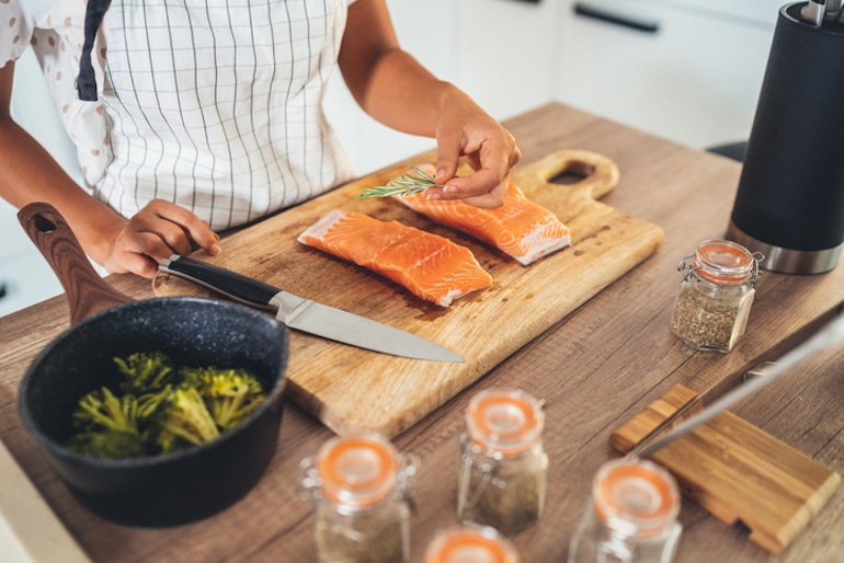 Woman preparing salmon with broccoli, two of the best foods for brain health and cognition
