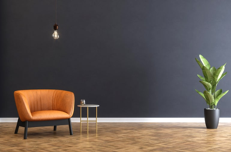 Minimalist home with blank black wall and orange leather armchair and plant