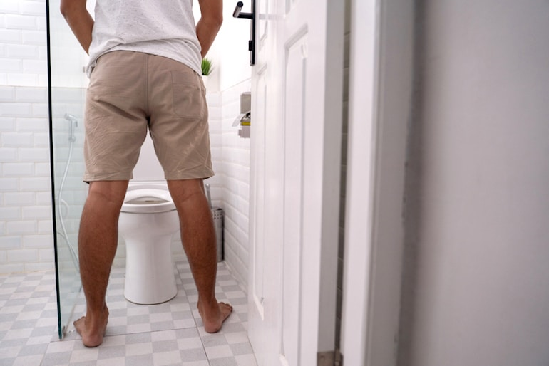Man peeing and thinking about what color of urine is normal