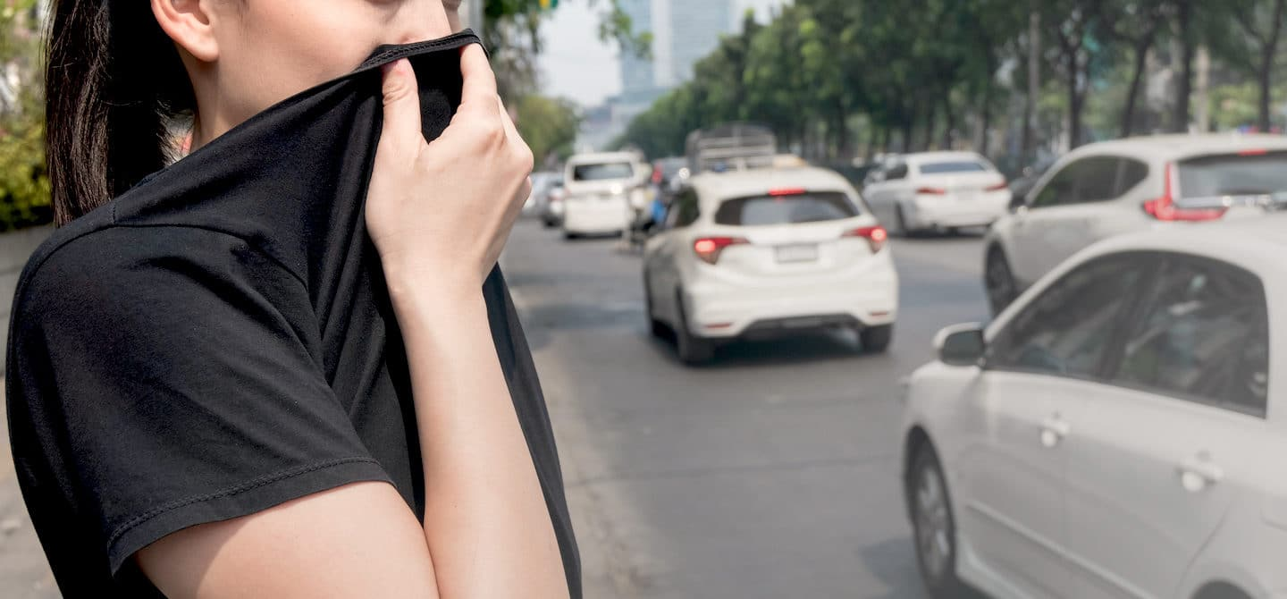 Woman covering her face on the sidewalk due to the bad effects of free radicals and cell damage from the environment on her health