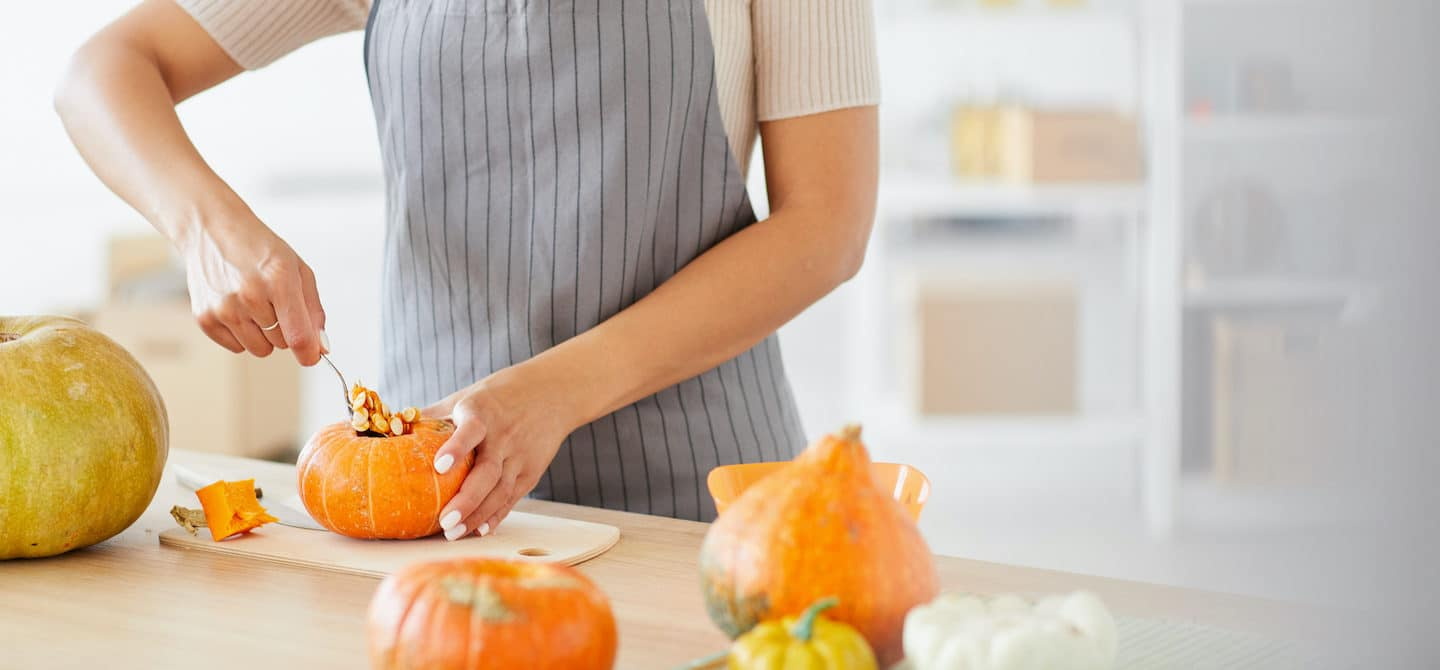 Woman scooping out pumpkin to cook to get their health benefits