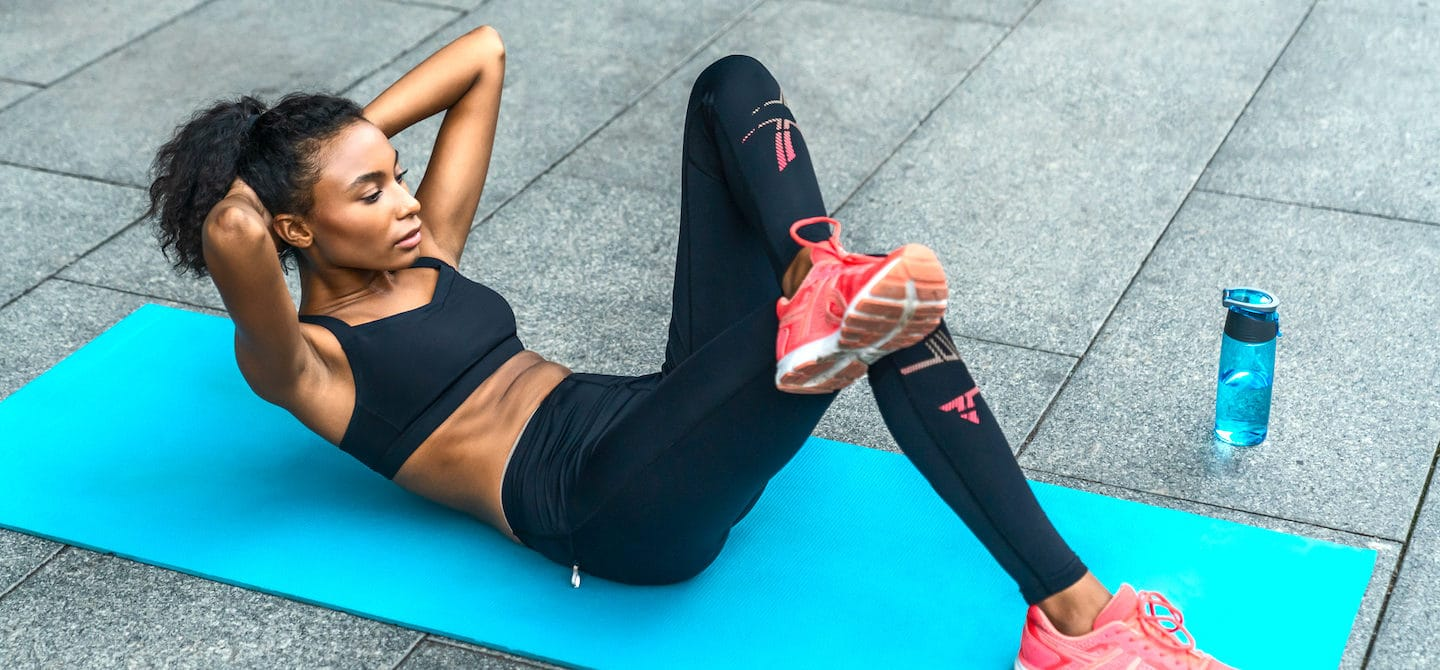 Woman doing a total ab workout outdoors