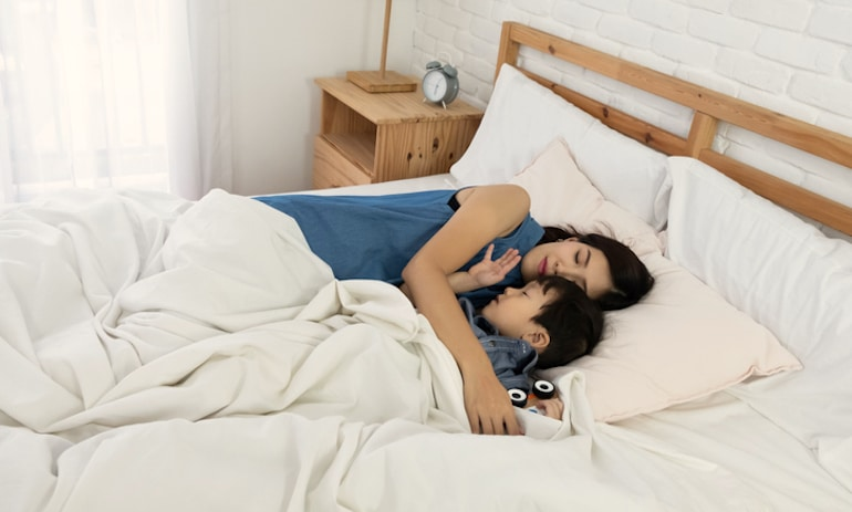 Mother and son sleeping with mouth closed, which encourages proper dental formation in children