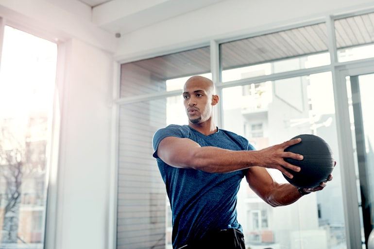 Man strength training with a weighted ball to get stronger, lose fat, and gain confidence