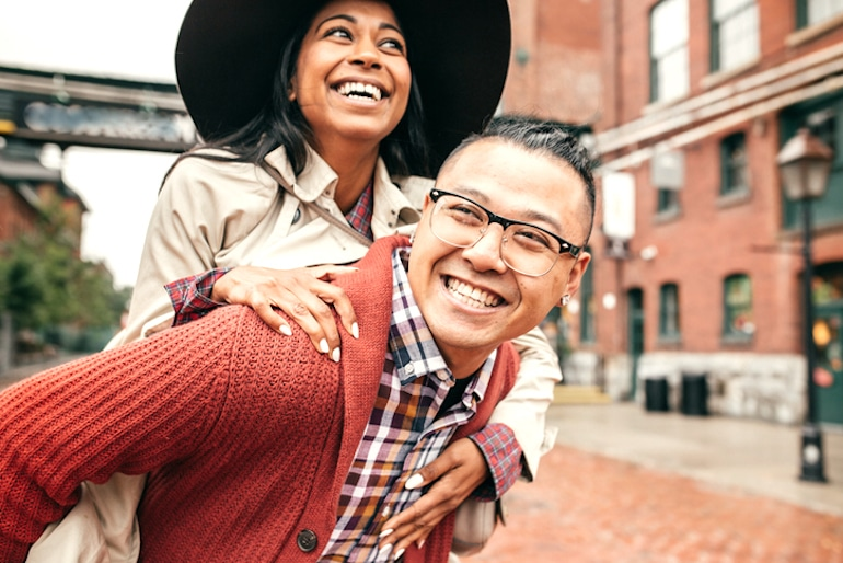 Woman wearing a large hat on friend's piggyback outdoors, smiling because hats don't make you lose hair or make your hair thinner