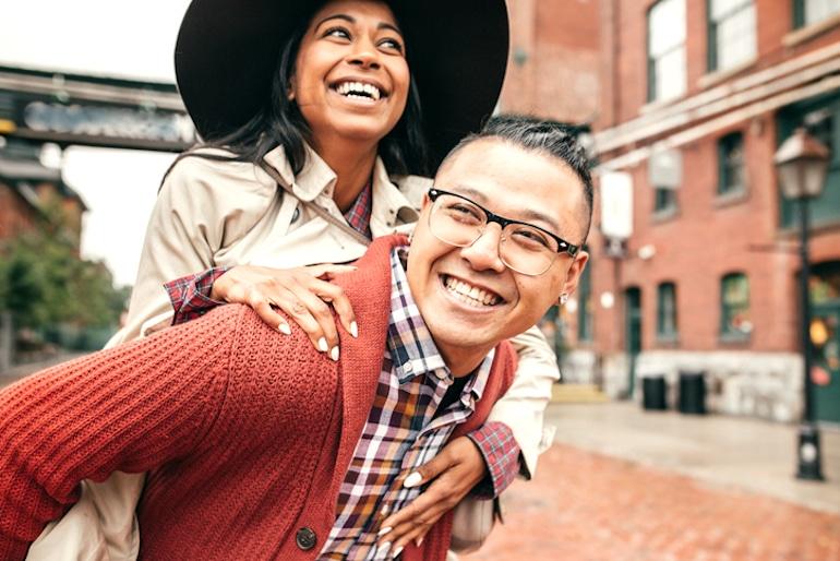 Mujer con un gran sombrero que lleva a cuestas a un amigo al aire libre y sonriendo porque los sombreros no te harán perder el cabello ni hacer que tu cabello se vuelva más delgado