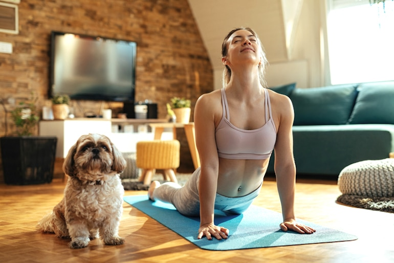 Woman doing yoga at home next to her dog, as one of the best exercises for stress relief