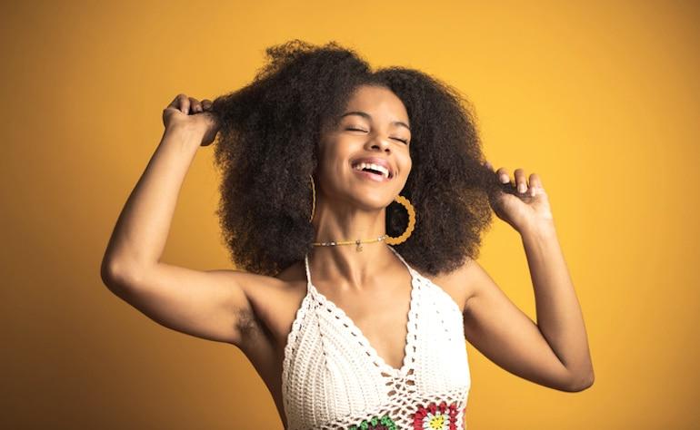 Mujer feliz mostrando su vello corporal femenino debajo de sus brazos; Concepto de positividad de vello corporal