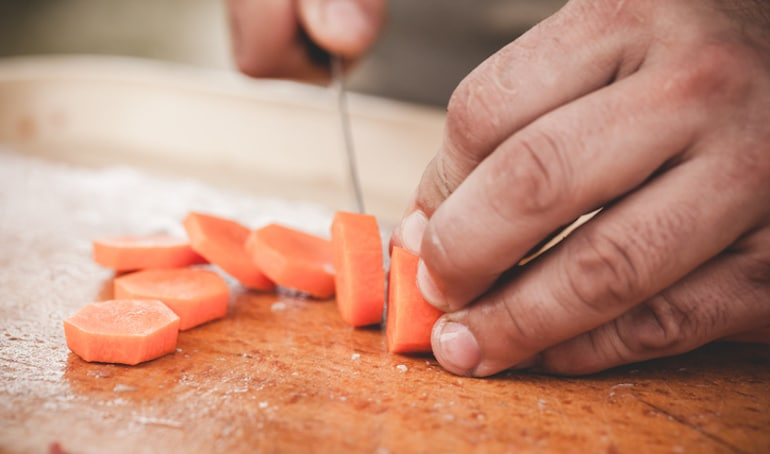 Man slicing carrots, one of the best foods to eat for sperm count and health