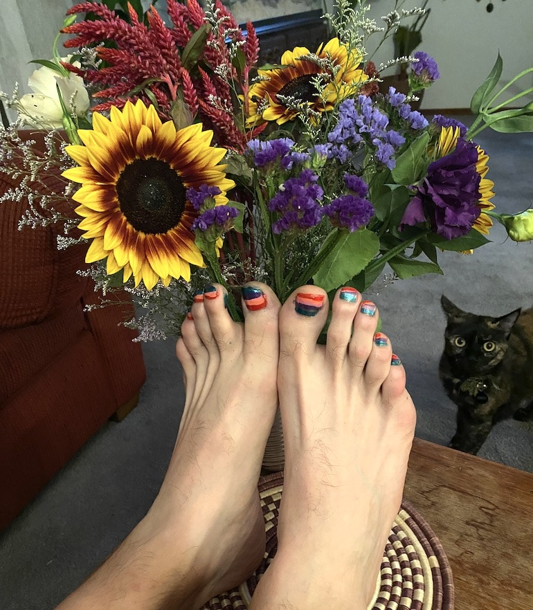 Man with colorful gel pedicure to illustrate that guys can wear nail polish