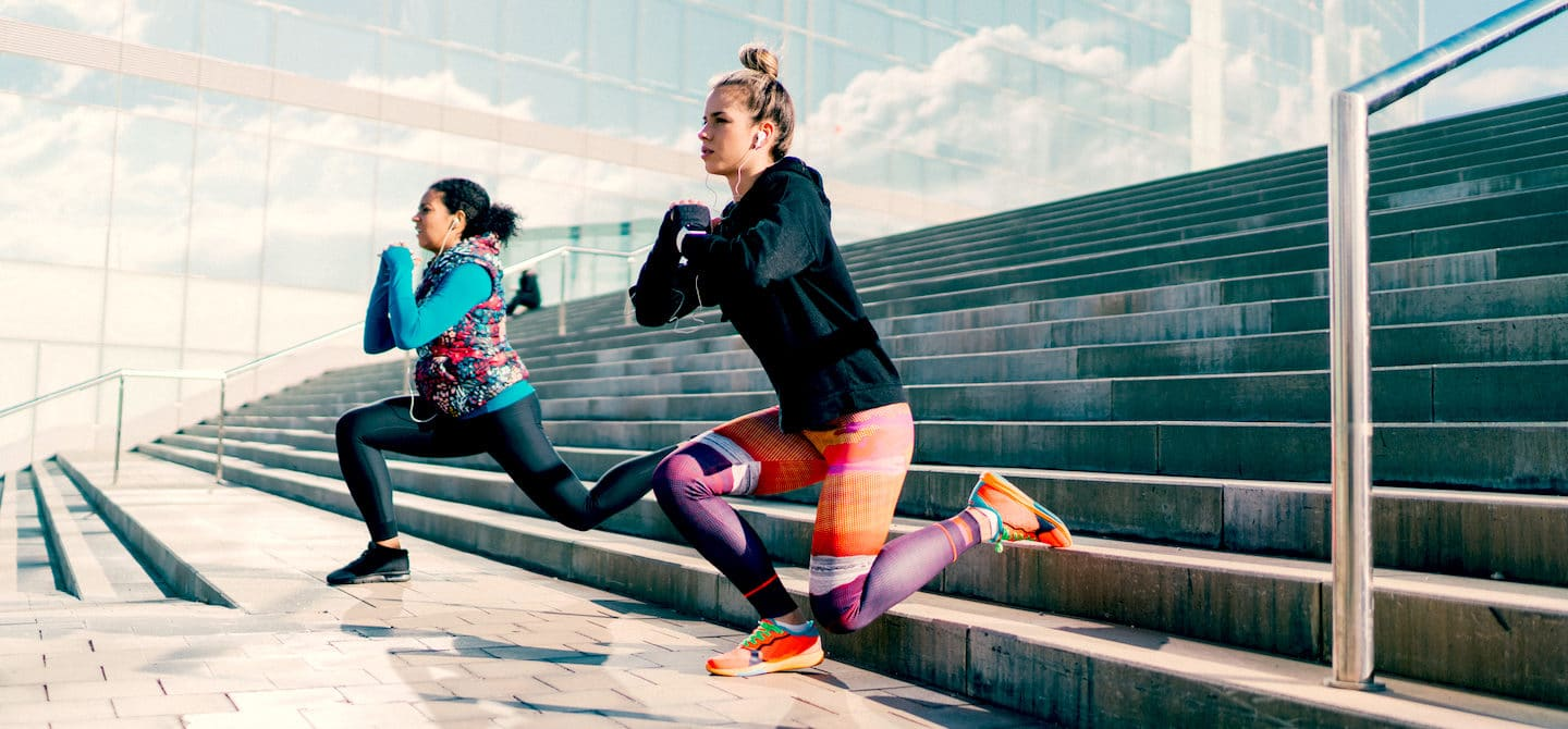 Two women doing lunges on stairs to reap the health benefits of strength training
