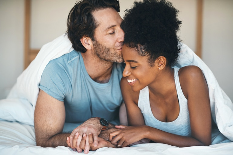 Man kissing wife in bed to illustrate healthy sperm and male fertility concepts