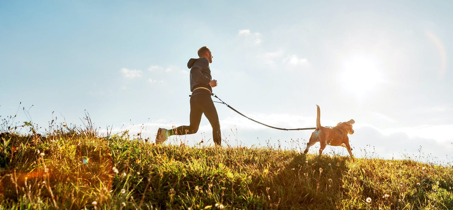 Man running with dog in nature to show how exercise reduces stress