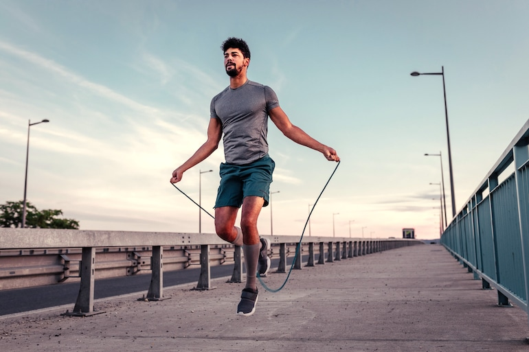 Man jumping rope outdoors to get in cardio to lose weight