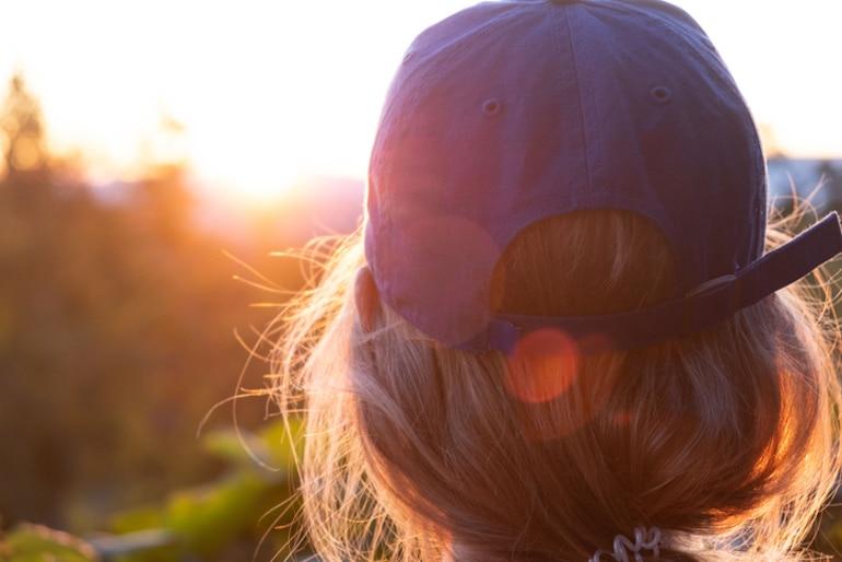 Detrás de la foto de una mujer con una gorra de béisbol al sol para proteger su cabello y cuero cabelludo de los rayos UV