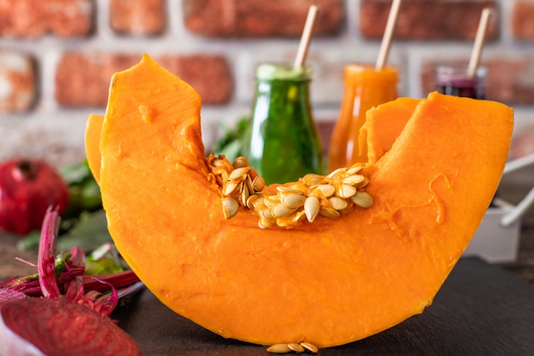 Cut pumpkin with seeds in front of healthy pressed juices, to illustrate the health benefits of pumpkin