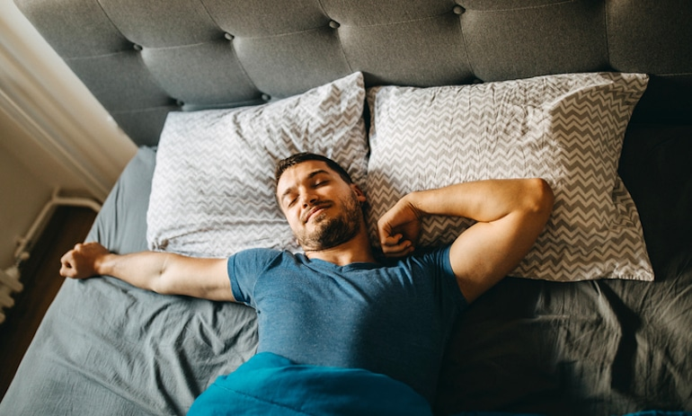 Man waking up and stretching in bed after a good night's sleep
