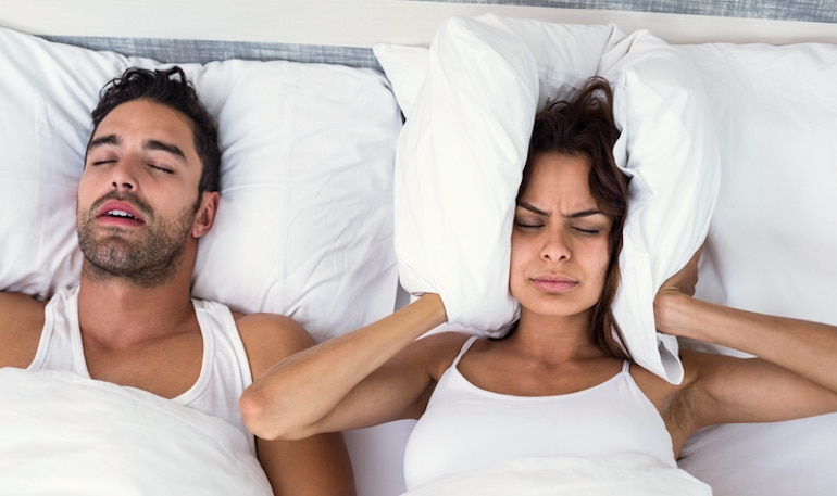 Woman blocking her ears with a pillow because her boyfriend is snoring and sleeping with his mouth open