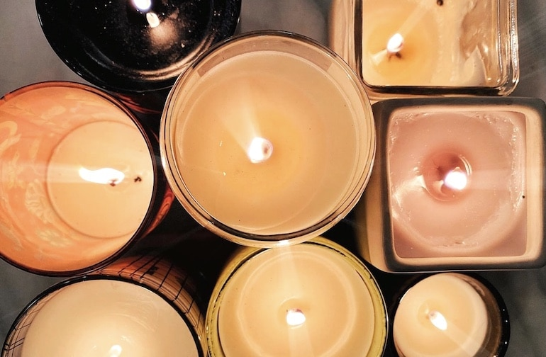 Collection of lit candles, a great addition to a self-care routine