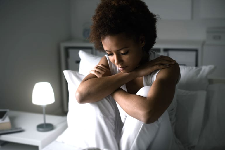 Woman stressed in bed to show how stress and sleep quality are related