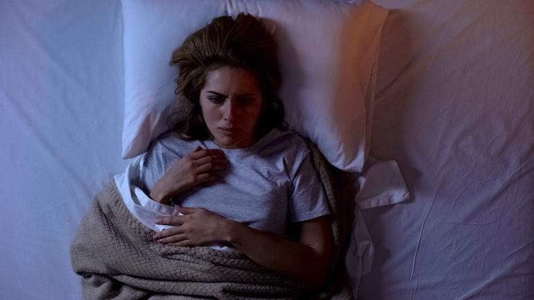 sueños vívidos en cuarentena Mujer despertando de un sueño de estrés en cuarentena