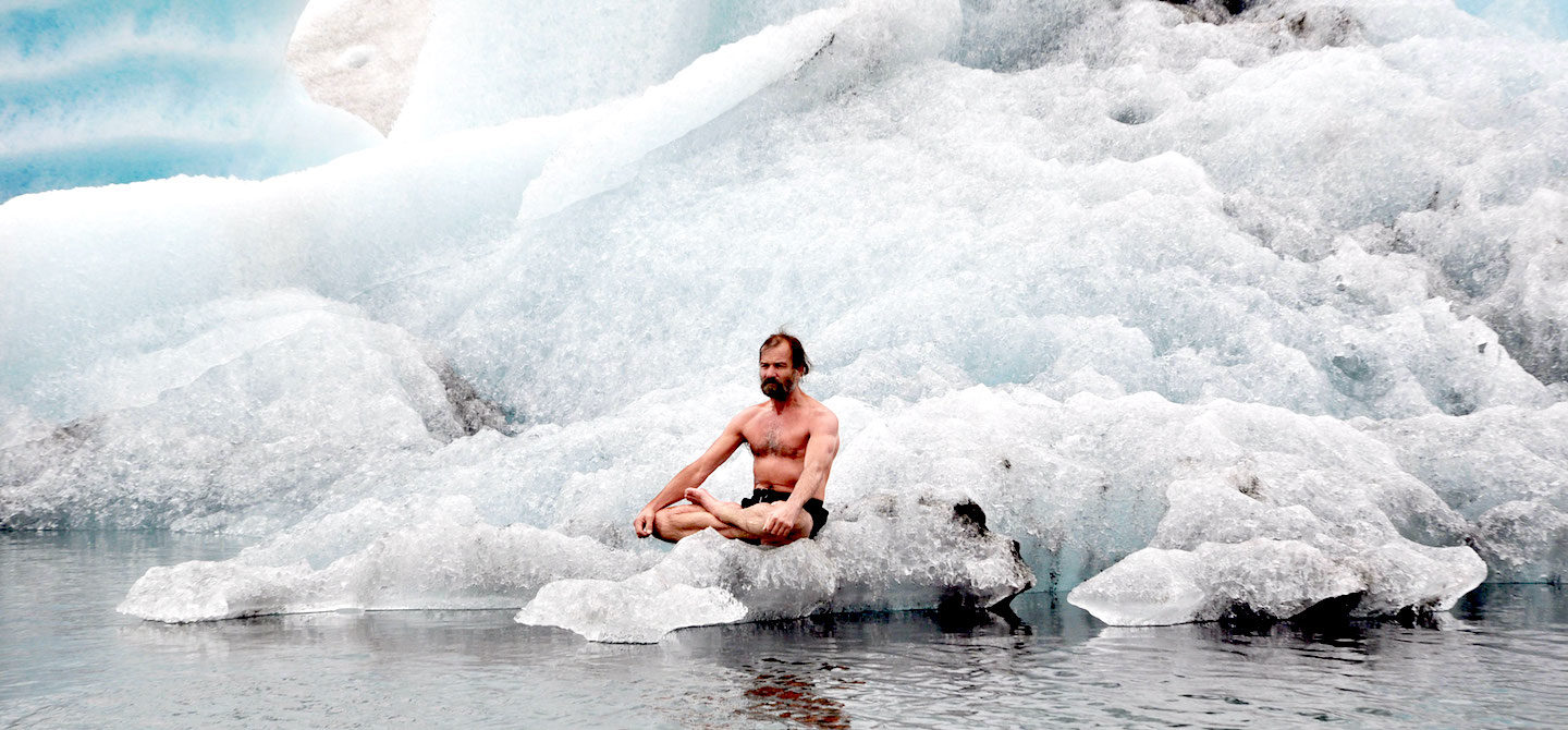 The Iceman Wim Hof sitting on a block of ice, practicing the Wim Hof Method of cold therapy and breathwork