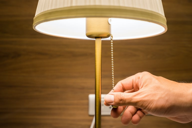 Person's hand turning off bedside lamp to prepare for sleep