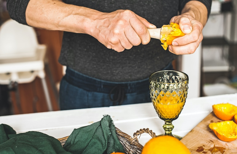 Man juicing oranges, since it's one of the best foods to eat for healthy sperm