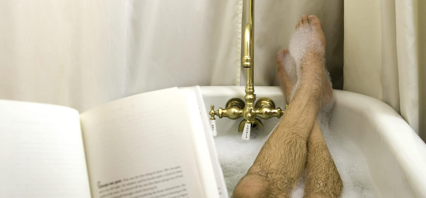 Man reading in bathtub to illustrate self-care for men ideas