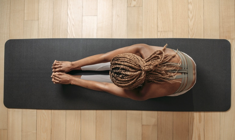 Overhead shot of woman stretching on yoga mat; yoga and Pilates low-impact training concept