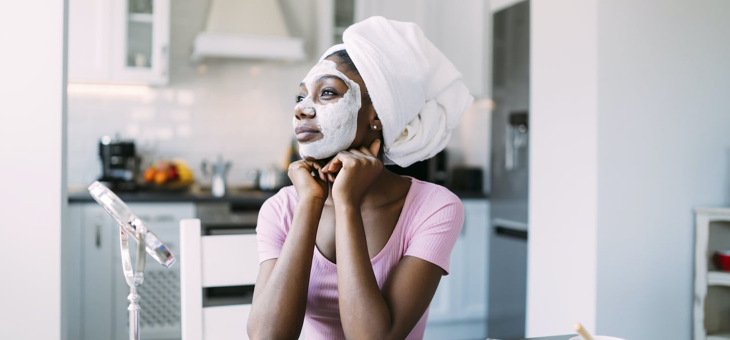 Woman sitting at kitchen table with a DIY hydrating face mask on to save her dry skin in the winter