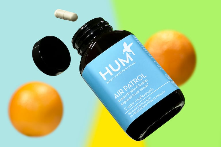HUM Air Patrol vitamin C supplement for immunity next to oranges on colorful background