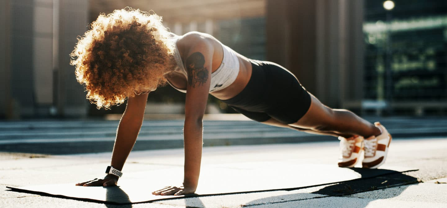 Woman in plank position exercising outdoors to boost her immune system
