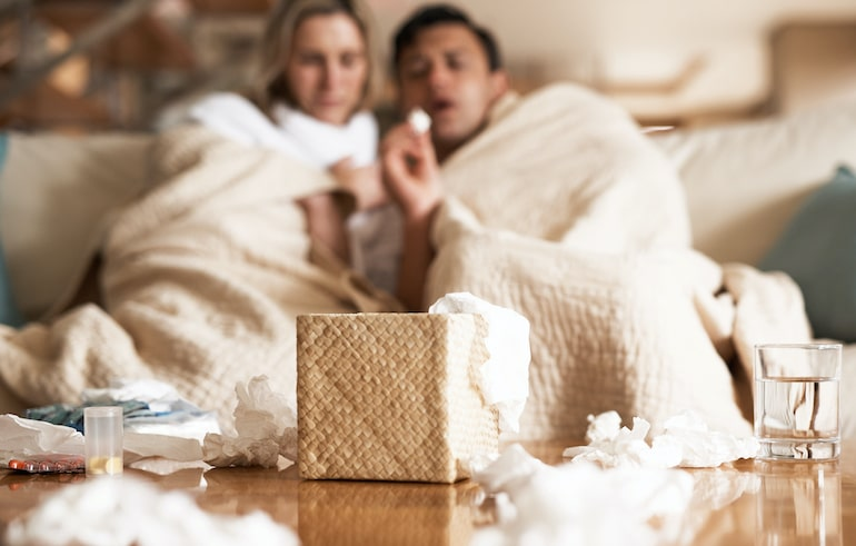 Sick couple on couch with dirty tissues