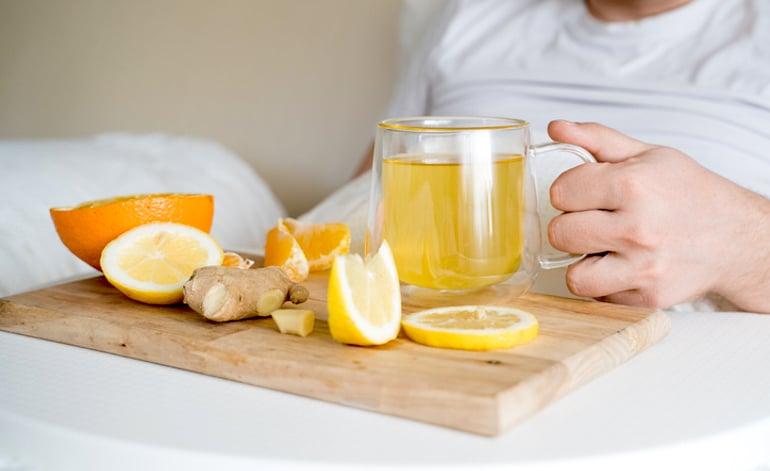 Hombre bebiendo té de jengibre con miel en la cama, que tiene tres de los mejores alimentos para comer cuando está enfermo