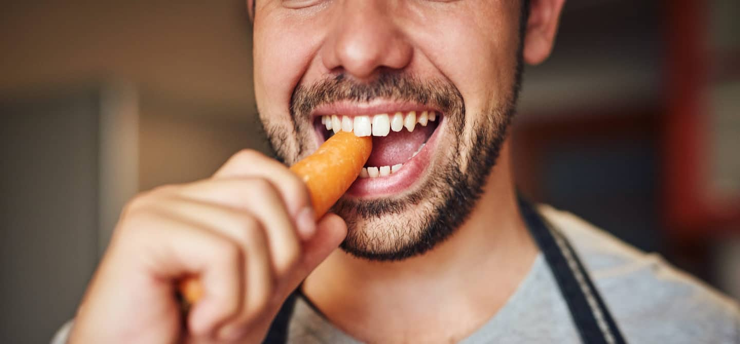Man chewing into a carrot to illustrate how many times you're supposed to chew your food