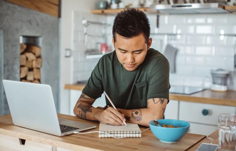 Hombre en la cocina escribe buenas preguntas para pedirle a un dietista que se prepare para su consulta