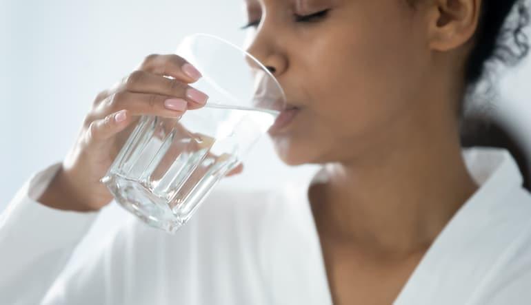 Mujer bebiendo agua con la esperanza de reducir los pedos y los pedos malolientes