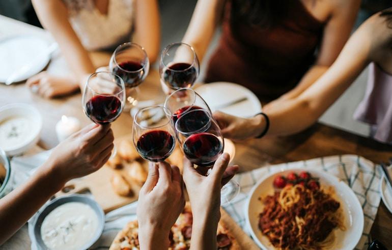 Amigos animando con vino para ilustrar cómo navegar las comidas sociales en un plan de comidas recomendado por nutricionistas