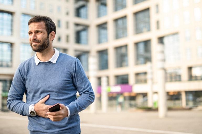 Hombre tocando el estómago con dolor mientras camina, preguntándose si tirarse pedos es saludable y normal