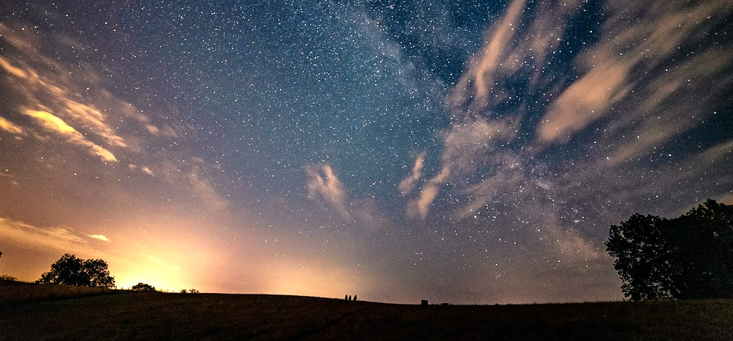 Bright night sky with blue and orange tones in a field; horoscope and astrology concept