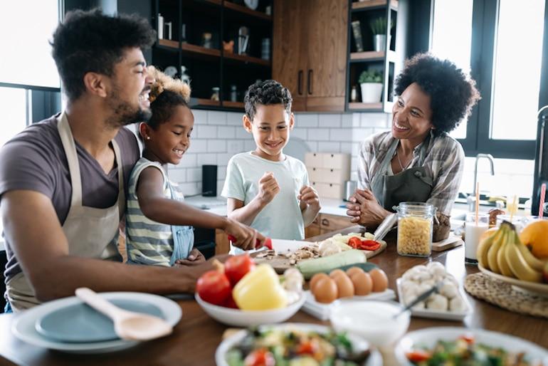 Familia de cuatro personas preparando una comida con verduras