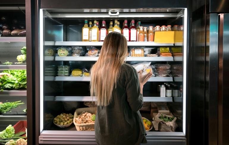 Mujer leyendo las etiquetas de los alimentos en una tienda especializada en salud para ver si cierta dieta es adecuada para ella