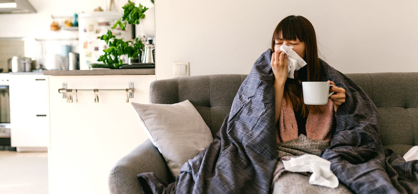 Woman sick at home on couch and drinking ginger tea, some of the best foods to eat when you're sick