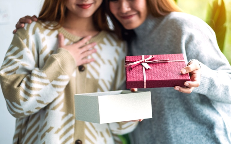 Friends exchanging presents, as giving to others can benefit your self-esteem