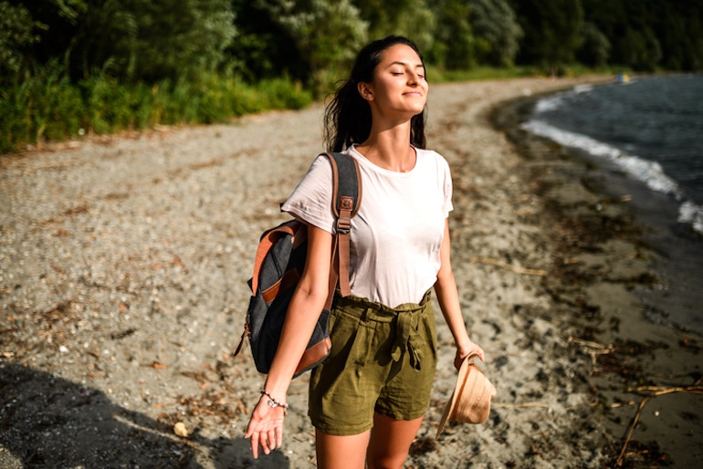 Calm and relaxed woman breathing in fresh air and enjoying the benefits of spending time in nature