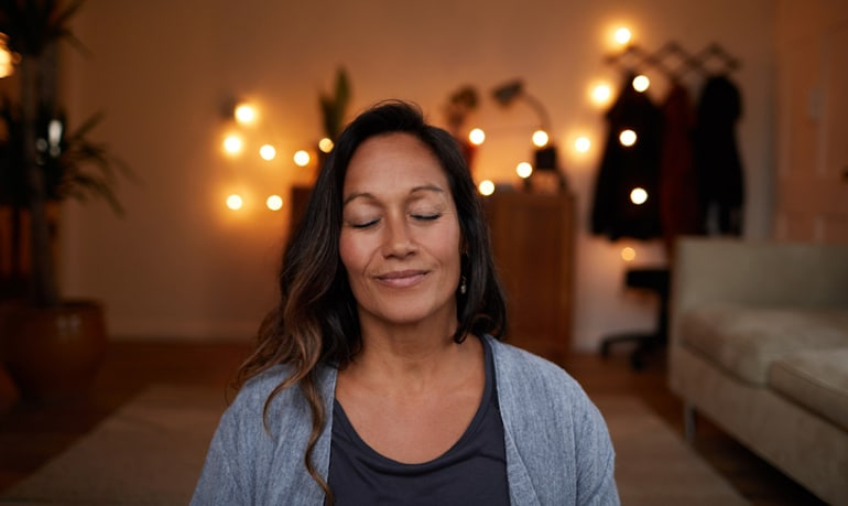 Serene woman practicing mindfulness at home for less stress, more happiness, and better emotional health